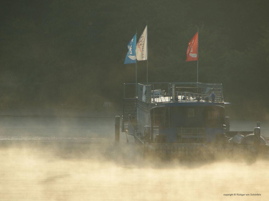 """Hausboot mit wehenden Fahnen bei """"dampfendem"""" Nebel in der Morgensonne / copyright © Rüdiger von Schönfels"""