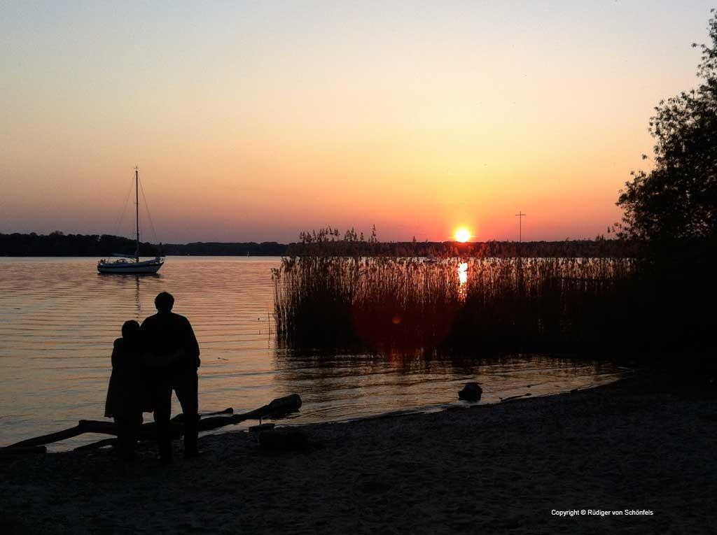 Liebespaar an der Havel im Sonnenuntergang mit Segelboot / copyright © R. v. Schönfels